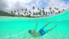 UNDERWATER: Young man in swimsuit swimming in perfect island lagoon - stock footage
