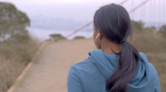 Ethnic girl listens to music while warming up for a run by Golden Gate bridge Stock Footage