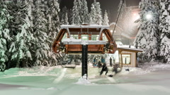Winter Resort Chairlift Loading Skiers and Snowboarders at Night Zoomed Out Stock Footage