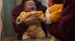 Father holding his 5 months old baby daughter in front of the mirror Stock Footage