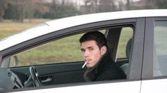 Young Man smoking cigarette while Driving Stock Footage