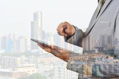 Double Exposure of Business Man using Mobile Tablet and Modern Building in th - stock photo