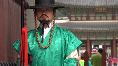 Soldier in traditional uniform posing for tourists in South Korean palace Stock Footage