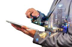 Double Exposure image of Businessman use Digital Tablet and City Building at  - stock photo