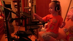 Young girl beginner in headphones play electronic drums at home - stock footage
