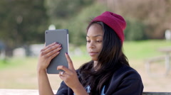 Urban African American girl uses her tablet outside in city park during the day Stock Footage