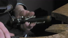 a craftsman repairing an old clarinet - stock footage