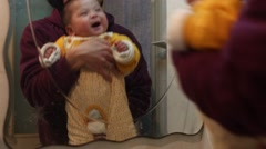 Tired, untidy father and his baby daughter playing in front of the mirror Stock Footage