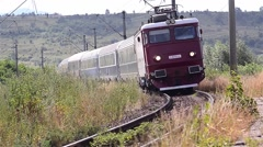 Train approaches a station after a long journey through the hills Stock Footage