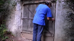 Man opens an old wooden gate and out into the cemetery next to the church Stock Footage