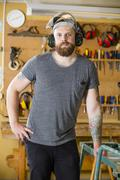 Confident craftsman with safety mask and earmuffs in workshop Stock Photos