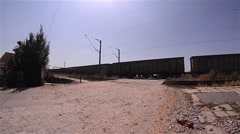 Freight train passing over a facility for passing cars over the railway equipped Stock Footage