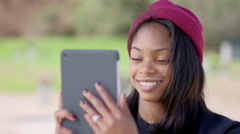 Happy young girl wearing engagement ring video calls fiancé with tablet at park - stock footage