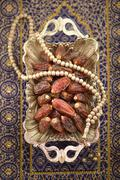 Ripened dates in a large silver ornamental platter with Islamic prayer beads - stock photo