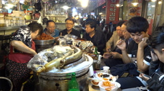 People get together to eat dinner in a popular night food market in Seoul city Arkistovideo