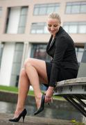 Portrait of a young business woman adjust her shoes - stock photo