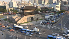 South Korea modern infrastructure, road traffic drives past ancient temple - stock footage