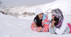 Giggling twins laying down at ski slope Stock Footage