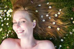 Close up portrait of a happy woman smiling with flowers in hair Stock Photos
