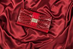 Red lacquer bag inlaid with diamonds lying on a red silk - stock photo