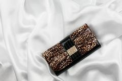 Black lacquer bag inlaid with diamonds lying on a white silk Stock Photos