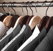 Shirts and jackets in wardrobe isolated closeup Stock Photos