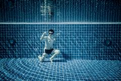 Underwater pool portraying Superman - stock photo