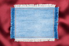 Frame made of denim fabric with yellow stitching on red silk - stock photo
