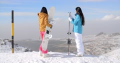 Two women snowboarders enjoying the winter view - stock footage