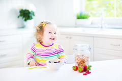 Beautiful toddler girl with curly hair wearing a colorful shirt having breakfast Kuvituskuvat