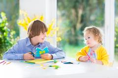 Two kids drawing, painting and cutting colorful paper butterflies - stock photo