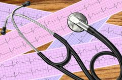 Heart analysis, electrocardiogram graph (ECG) and stethoscope over wooden tab - stock photo