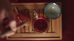 Man pours red tea in a porcelain bowl Stock Footage