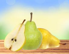Beautiful fresh green and yellow pears on wooden table over nature background - stock photo