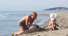 Mom and daughter are building a sand castle Stock Footage