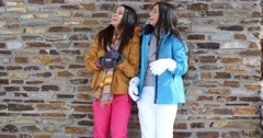 Cute twins in winter coats leaning on wall Stock Footage