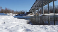 Winter river with open water under the bridge - stock footage
