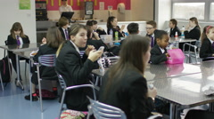 4K Happy young school children eating packed lunches in school cafeteria - stock footage