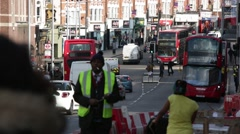 Clapham Junction: traffic and red busses, London, England Stock Footage
