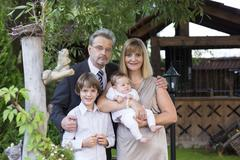 Stock Photo of Beautiful mature couple in formal dress and suit with two kids in a garden