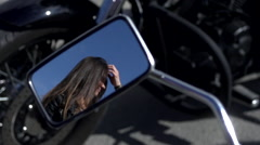 Girl straightens her hair in the rearview mirror of bike - stock footage