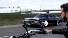 Biker looking on riding Buick Reveira in slow motion Stock Footage