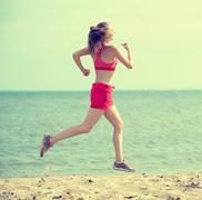 Young lady running at the sunny summer sand beach. Workout.  Jog Kuvituskuvat
