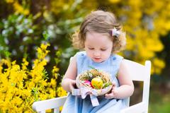 Cute curly toddler girl enjoying easter egg hunt in the garden - stock photo