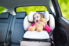 Cute curly toddler girl with a toy bear enjoying a car ride in safe baby seat - stock photo