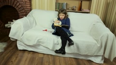 Little girl reading a book in the living room on the couch. Stock Footage