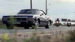 Muscle car and bikers ridding on the road Stock Footage