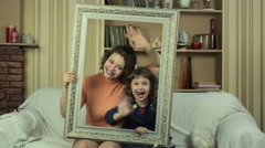Mother and daughter posing with picture frame on the couch in the living room. - stock footage