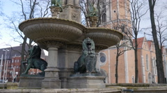 4k Fountain monument Braunschweig with lion sculpture and church tower Stock Footage