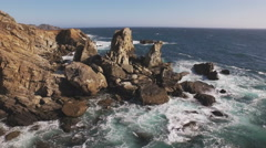 Aerial over Jagged Pacific Coastline Rocks and Surf 4K Stock Footage